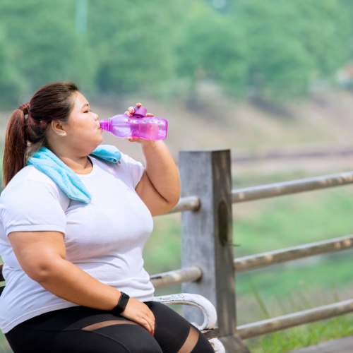 woman drinking water post-workout