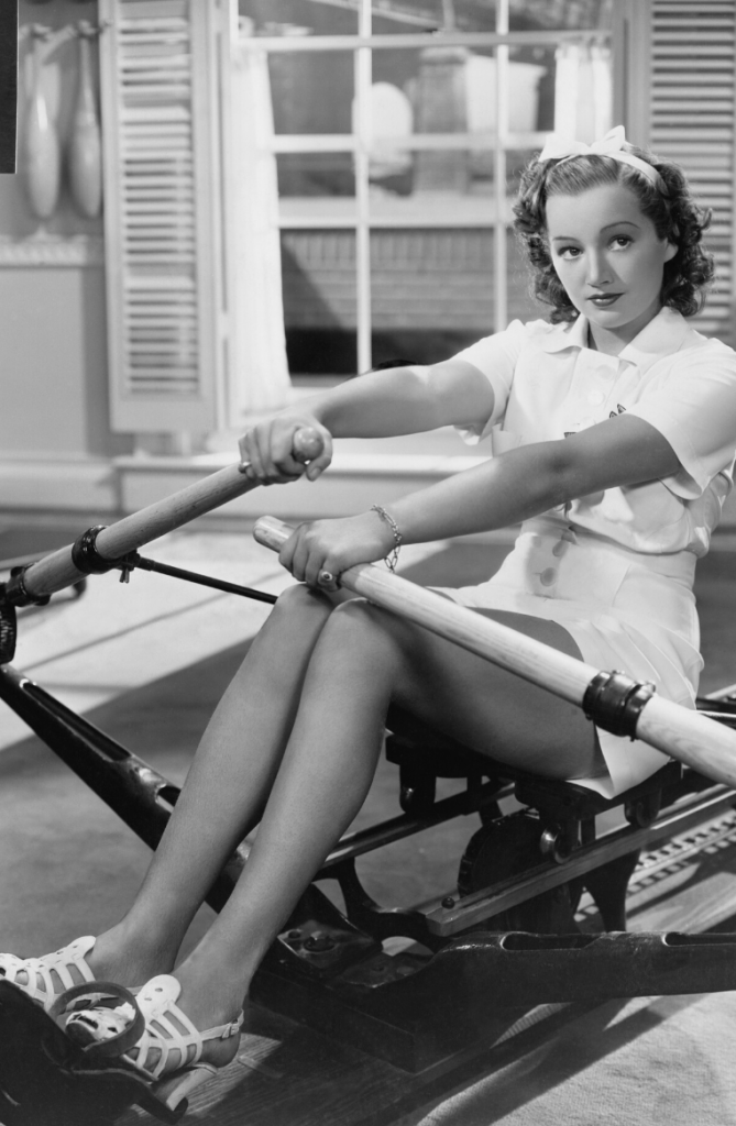 black and white photo of 1950s woman on rowing machine