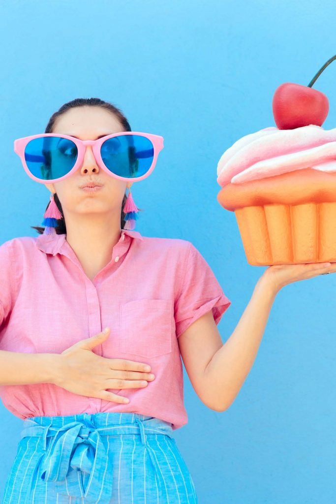woman holding a cupcake and rubbing her stomach