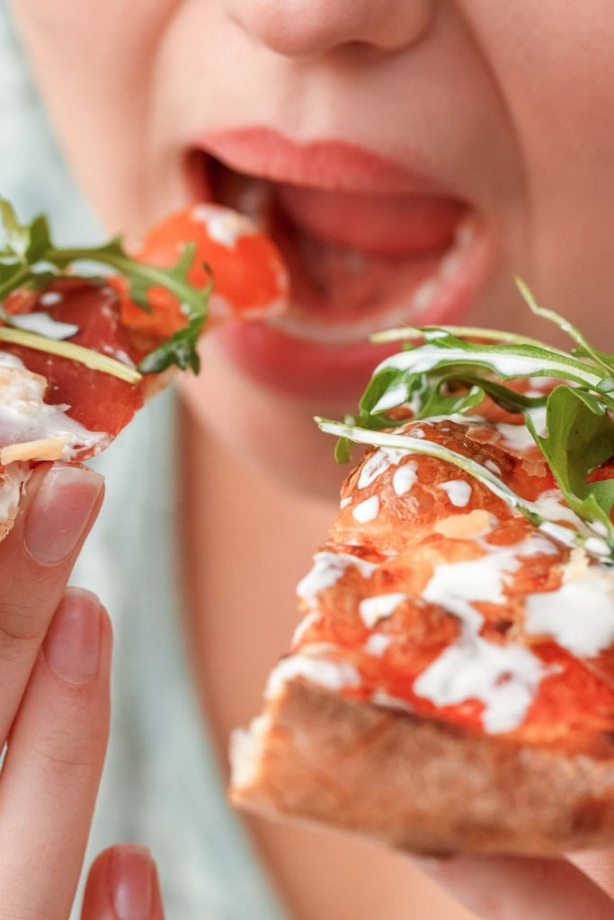 closeup of woman's mouth eating pizza